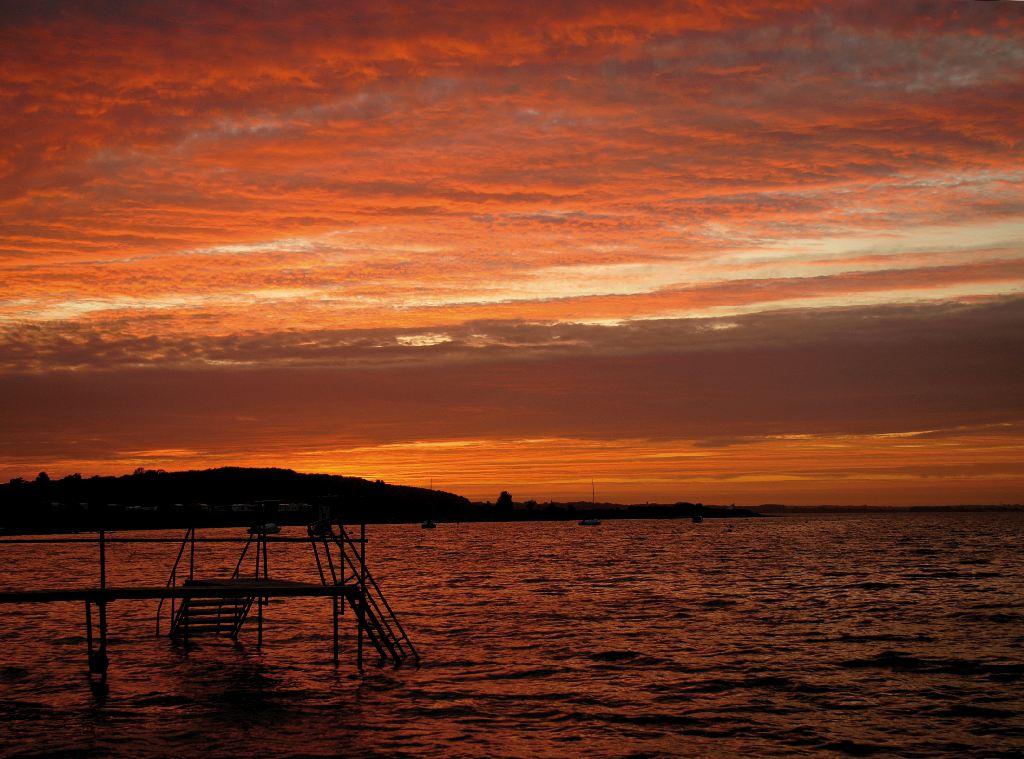 Ein orange gelber Himmel über der Ostsee sorgt für einen schönen Urlaub.