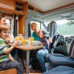 Wohnmobile für die ganze Familie: Vater, Mutter und zwei kleine Kinder sitzen gemütlich am Frühstückstisch.