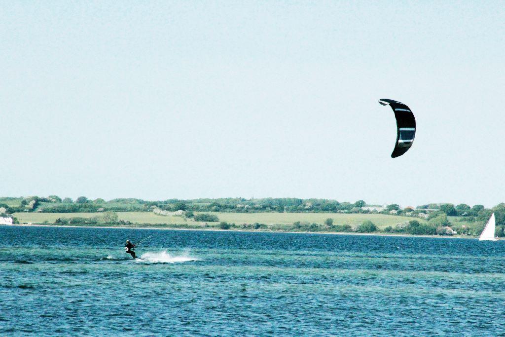 An der Ostsee surfen oder kiten: Auf der Flensburger Förde surft ein Mensch mit einem Kiteschirm.