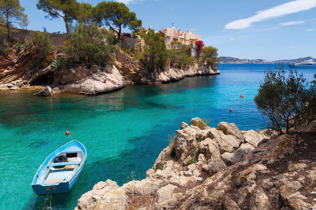 Ein kleines Boot schwimmt in einer türkisgrünen Bucht mit steinigen Ufern auf den Balearen.