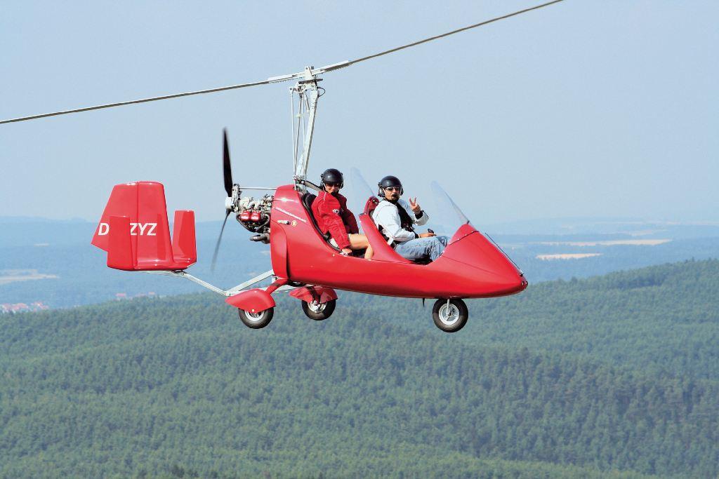 Urlaubserlebnisse: Ein kleiner roter Hubschrauber mit zwei Personen an Bord fliegt über einen Wald