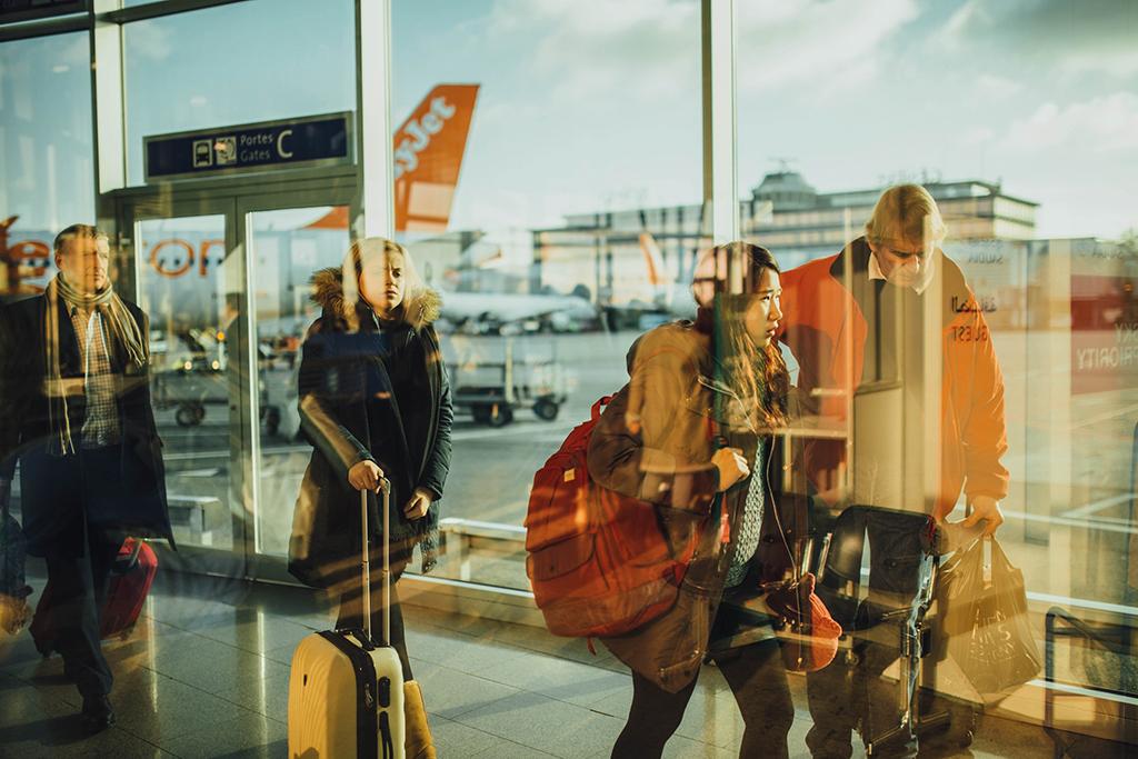 Ankommende Passagiere auf einem Flughafen – Sparen im Urlaub