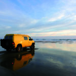 Yellow 4x4 RV van on deserted beach, Wohnmobil
