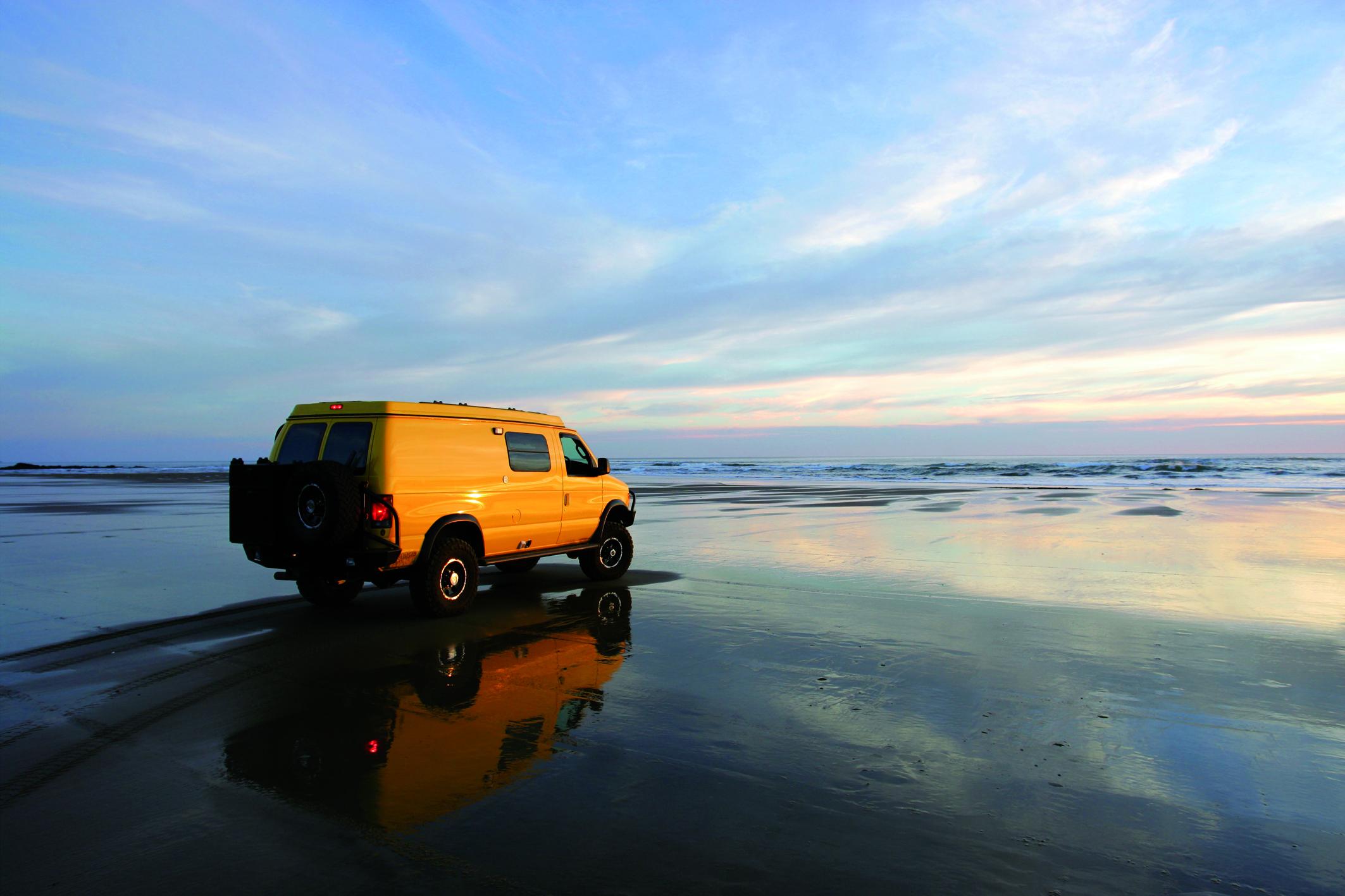 Yellow 4x4 RV van on deserted beach, Wohnmobil
