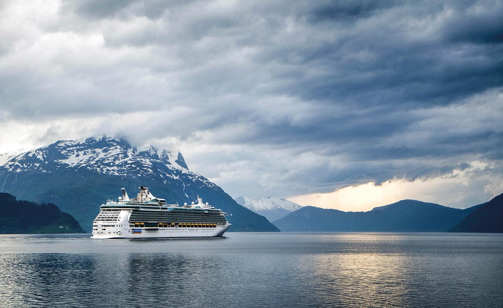 Schiff auf einer Kreuzfahrt vor Gebirge.