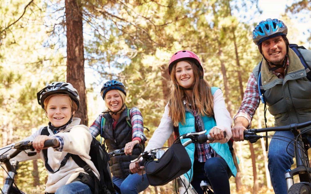 Familienurlaub mit dem Rad: Vater, Mutter, Tochter, Sohn auf Mountain-Bikes lächeln in die Kamera.