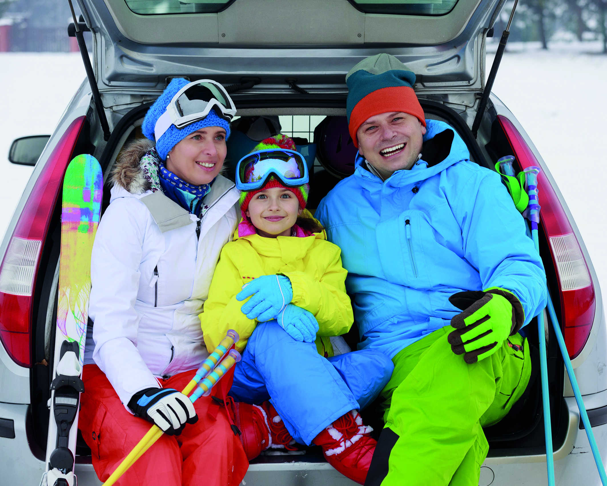 Vater, Mutter, Tochter sitzen in Skianzügen bei geöffneter Heckklappe im Auto im Winterurlaub.