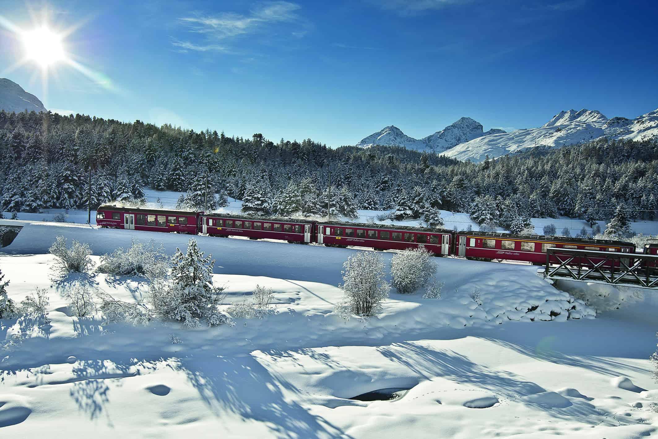 Alpen entdecken: Die Rhätische Bahn fährt durch die Winterlandschaft der Schweiz.