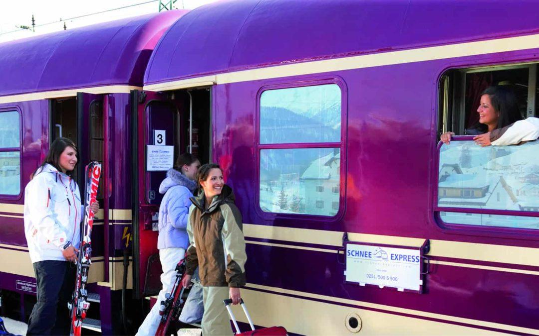 Reisende am Zug mit Ski und Gepäck auf dem Weg in den Winterurlaub.