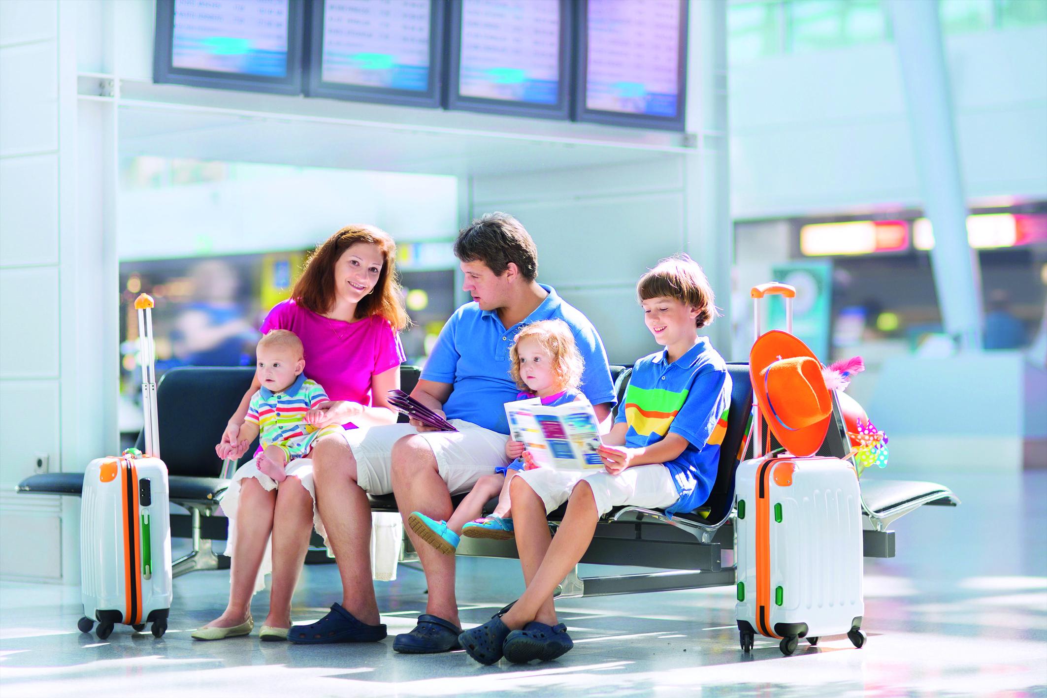Eine Familie sitzt zufrieden auf einer Sitzgelegenheit im Flughafen. Sie haben alle Reisevorbereitungen im Voraus getroffen und sind nun bereit für den gemeinsamen Urlaub.