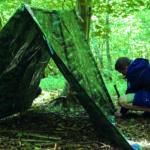 Ein Teilnehmer des Survival-Camps in der Wildnis Deutschlands baut sein Zelt auf