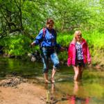 Zwei Frauen wandern durch einen Fluss (Ostseeurlaub).