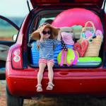 Ein Kind sitzt im geöffneten Kofferraum.