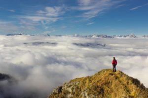 Ein Mann steht über den Wolken auf einem Berggipfel.