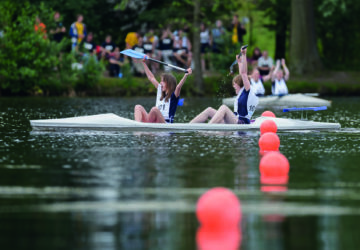 Zwei Teilnehmer sitzen im Kanu, freuen sich und heben ihre Paddel in die Luft (Betonkanus).