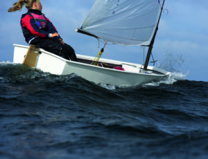 Eine Frau segelt alleine ein weißes Boot (Ostsee).