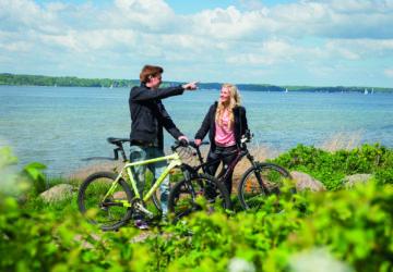Zwei Fahrradfahrer machen vor der Ostseeküste Pause.