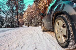 Ein Auto fährt auf einer schneebedeckten Straße (Skiurlaub mit dem Mietwagen).