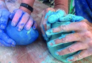 Zwei Menschen formen bunt eingefärbten Ton mit ihren Händen (Urlaub und Kunst).
