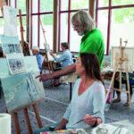 Eine Frau hält einen Pinsel in der Hand und schaut auf ein Gemälde. Ein Mann steht neben ihr und zeigt auf eine Stelle des Bildes (Urlaub und Kunst).