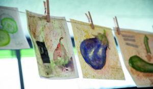 Eine Reihe von selbstgemalten Bildern, hängend an einer Schnur (Urlaub und Kunst)